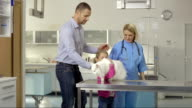 Father And Daughter Bringing A Cat To The Clinic video