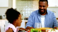 Father and daughter having meal on dinning table at home video