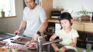 Father and daughter making together a lunch in kitchen video