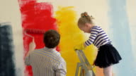Father and daughter painting walls in bright colors video