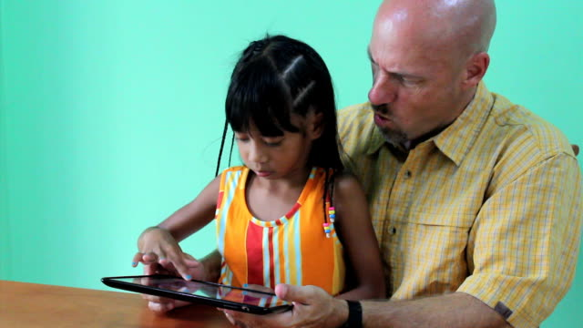 Father And Daughter Playing Game On Digital Tablet video