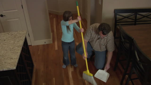 Father and daughter sweeping floor video