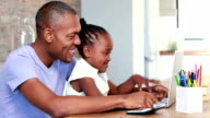 Father and daughter using a laptop video