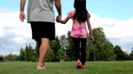 Father And Daughter Walking Through Field On Summers Day video