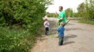 Father and happy children play with rods outdoors video
