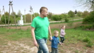 Father and happy children walk together outdoor video