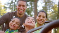 Father and his daughters smiling on a merry-go-round video