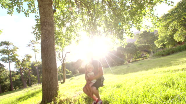 Father and his laughing son enjoy summer sunset on swing video