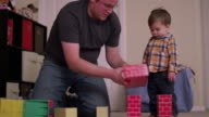 Father and his young son playing with cardboard blocks video