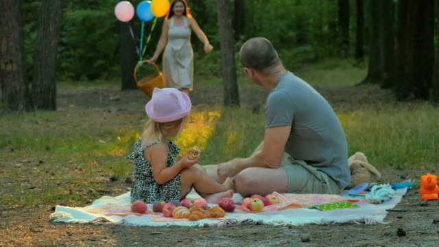 Father and little girl relaxing on blanket in park and wait woman with basket video