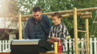 Father and Son Are Cooking Burgers on Grill at Bright Summer Day. video
