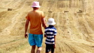 father and son are going on a field near the haystacks mown field video