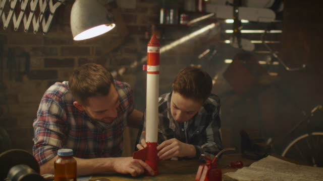 Father and son are modeling a toy rocket in a garage at home. video