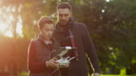 Father and Son Controlling Dron with Remote Control in the Park video