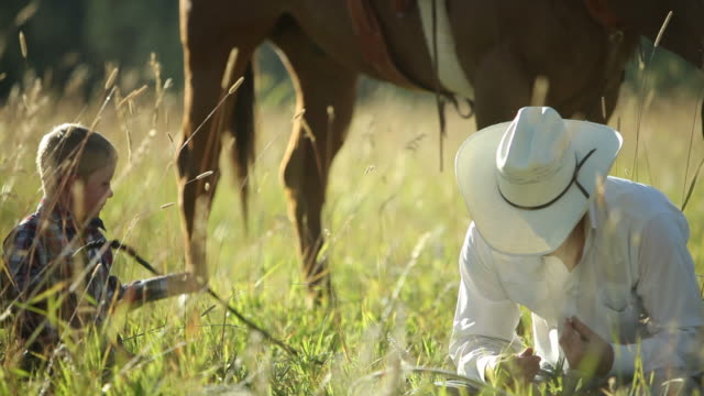 Father and son cowboys sit in grass taking break video