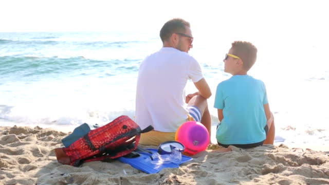 Father and son enjoy in sunrise on the sand video