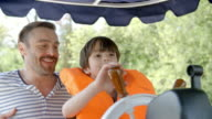 Father And Son Enjoy Ride In River Boat Shot In Slow Motion video