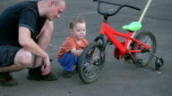 Father and son fixing bicycle tire on sidewalk video