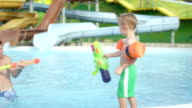 SLOW MOTION: Father and son having a water gun fight in a pool on a beautiful summer day in water park video