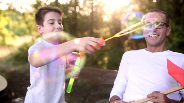 Father and son having fun soap bubbles outdoors video