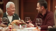 Father and son in law chatting at Thanksgiving dinner video