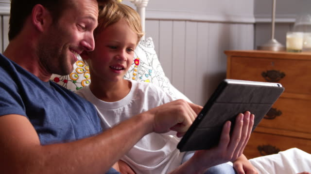 Father And Son Looking At Digital Tablet In Bed Together video