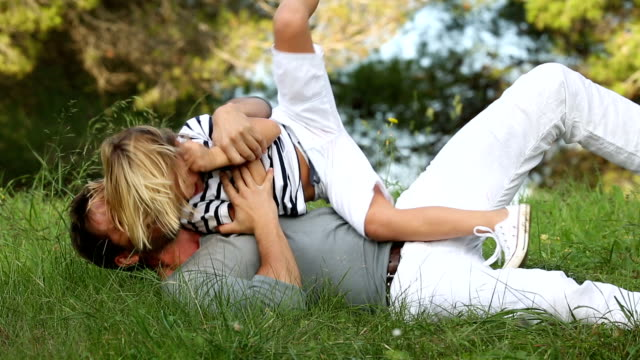 father and son lying in the grass having fun video