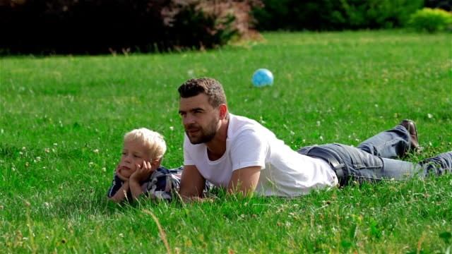Father and son lying on the grass in park video