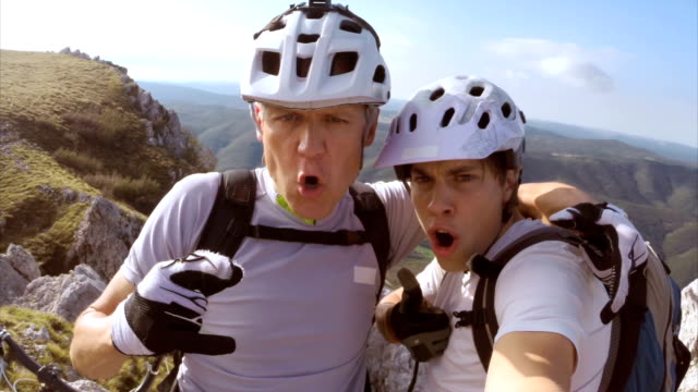Father and son making funny selfies on top of mountain video