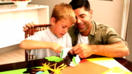 Father and son making paper shapes together at the table video