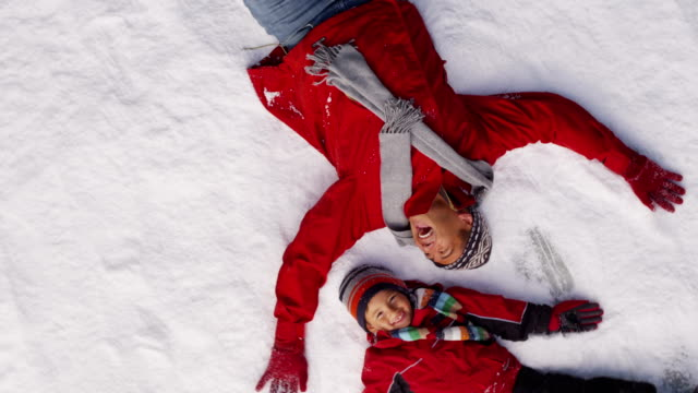 Father and son making snow angels video