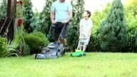 HD: Father and son mowing grass in a backyard. video