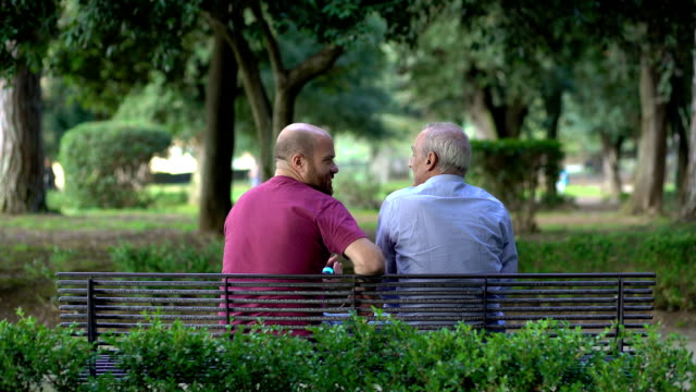 father and son on a bench in a park, talking and comparing video