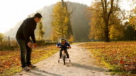 Father and son on the bicycle outdoor in the autumn park video