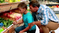 Father and son picking out pepper in supermarket video