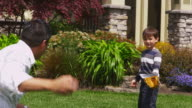Father and son playing baseball in yard video