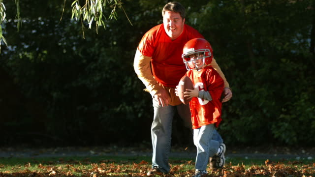 Father and son playing football in Fall, slow motion video