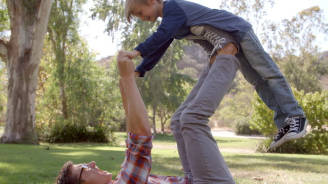 Father and son playing on the grass in a park video