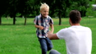Father and son playing on the grass in park video