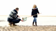 MS Father and son playing with fishing net on beach video