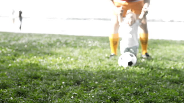 father and son playing with soccer ball on the grass video
