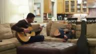 Father and son practicing on their guitars in the living room video