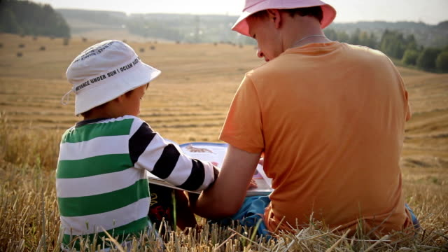 father and son reading a book on top of a mountain in the field, a great review video