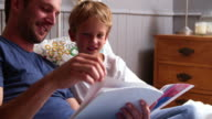 Father And Son Reading Book In Bed Together video