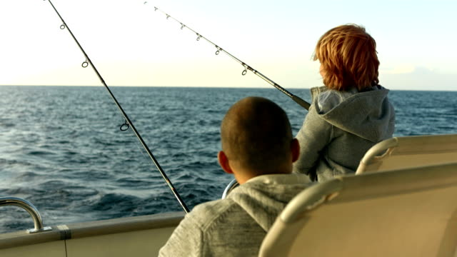 HD: Father And Son Reeling In A Fish video