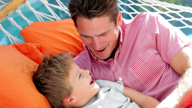 Father And Son Relaxing In Garden Hammock Together video