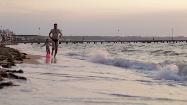 Father and son running along the beach with ball video