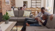 Father And Son Sit On Sofa In Lounge Using Digital Tablet video