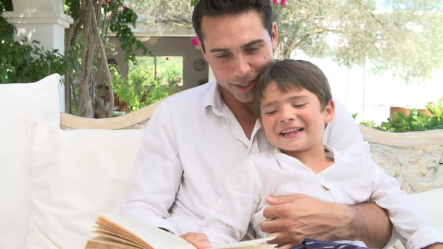 Father And Son Sitting In Garden Reading Book Together video