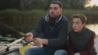 Father and Son Sitting in the Boat Fishing. Father Swings Fishing Rod. video